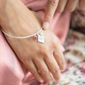 silver plated scalloped charm bangle with initial charm and birthstone